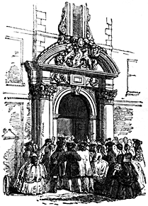 A crowd stands around an archway.