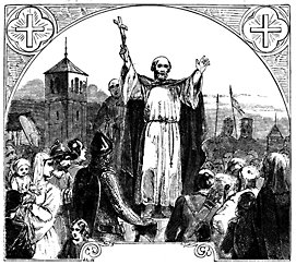 A man stands on a raised platform in the midst of a crowd. His arms are raised and his right hand holds a large cross.