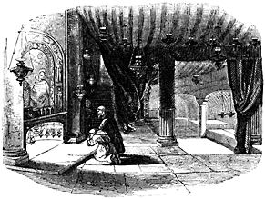 A man kneels at a low altar in a heavily draped room.