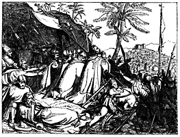 Men are praying near a rock outside of a city.